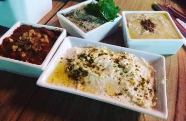 Babagnoush, pasta de grão de bico, pasta de pimentão vermelho e coalhada com azeite e Zatar.
