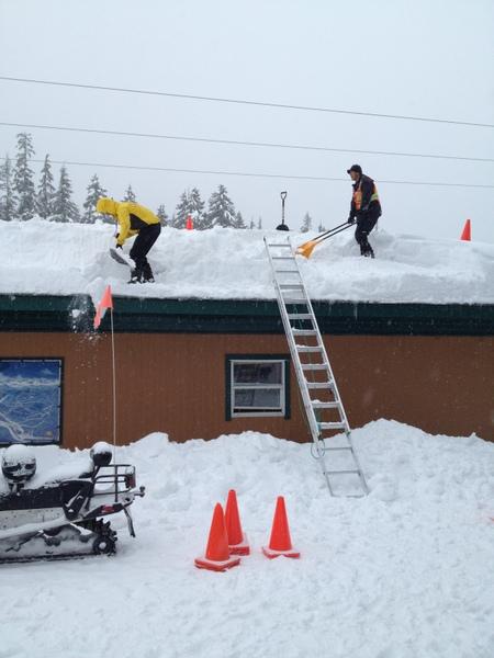 工作人员正忙于铲雪,要不这屋顶要垮了。