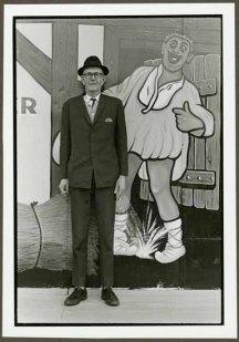 "VPL 88674 ""Portrait of a tall man standing in front of a street mural"". Nina Raginsky. 1972."