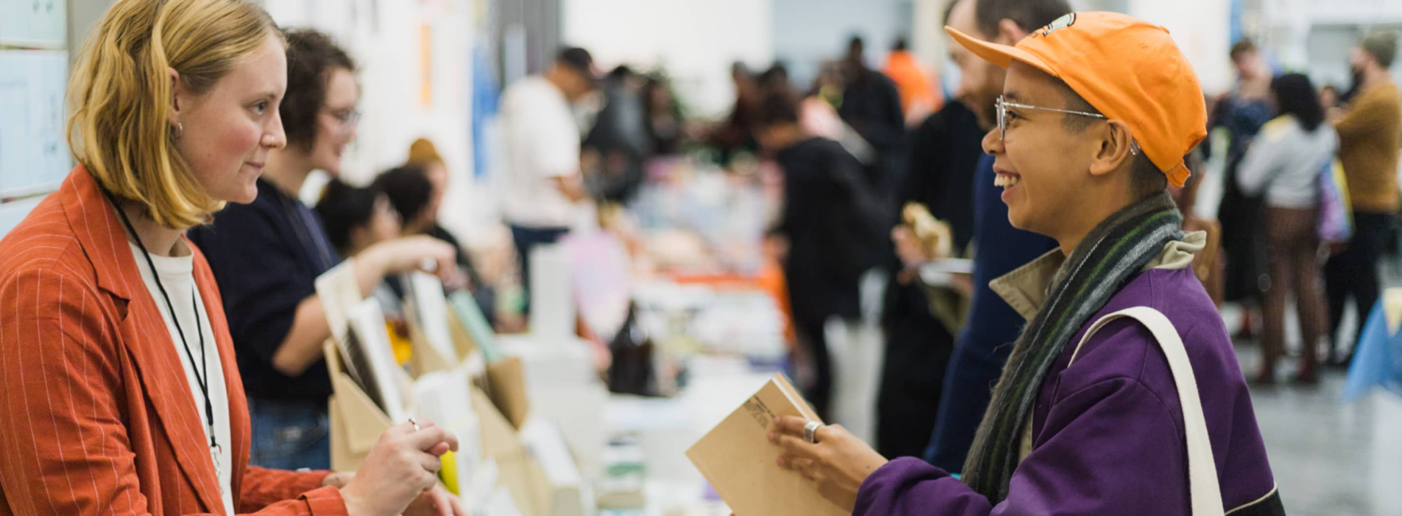 Photograph from VABF 2019 of an exhibitor (wearing an dark orange blazer) standing behind their table of books and exchanging a smile with an attendee, wearing an orange baseball cap and holding a zine with a light beige cover.