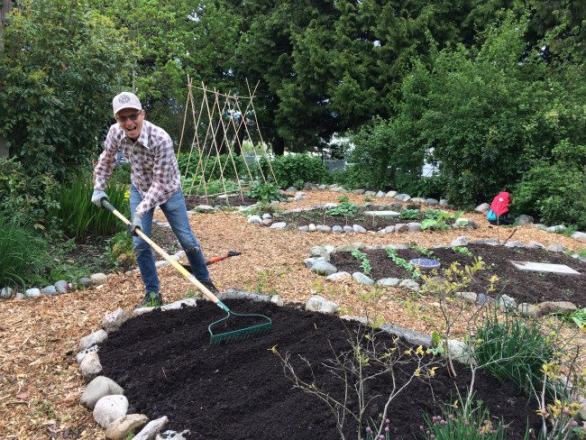 An image of Ian raking the garden, with a big grin on his face