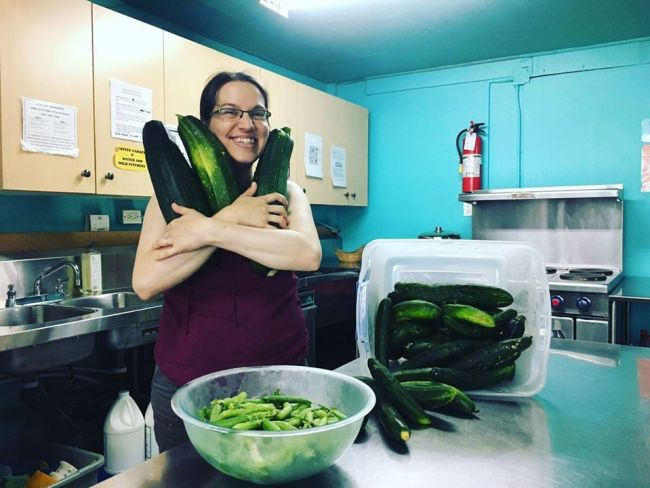 An image of a person hugging an armload of zucchinis in the kitchen