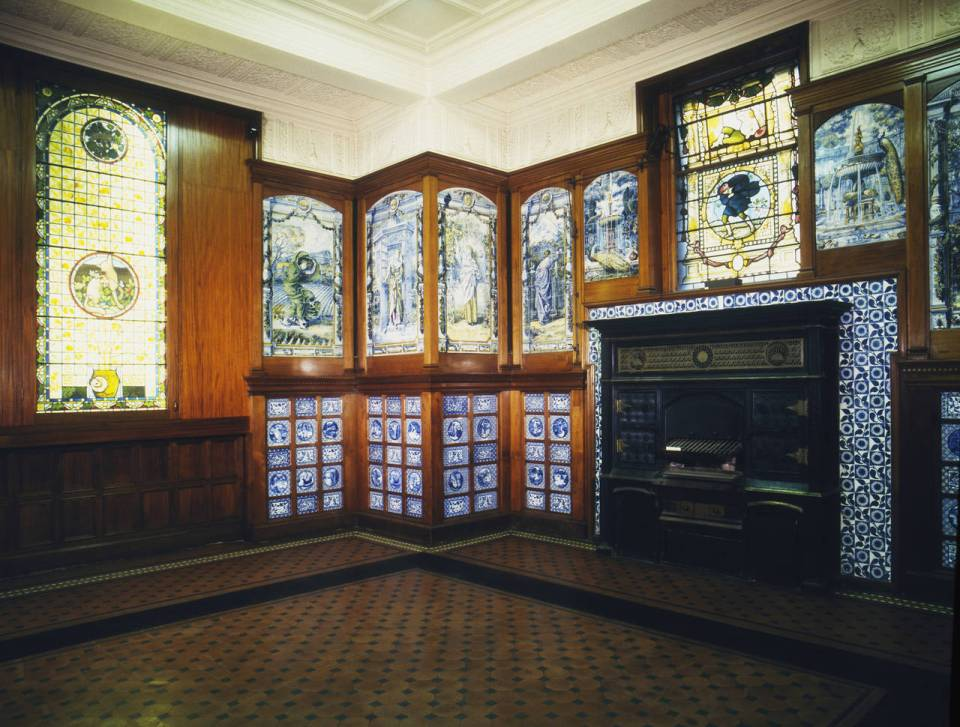 Blue porcelain wall decoration, stained glass windows and iron fireplace in Poynter room V&A