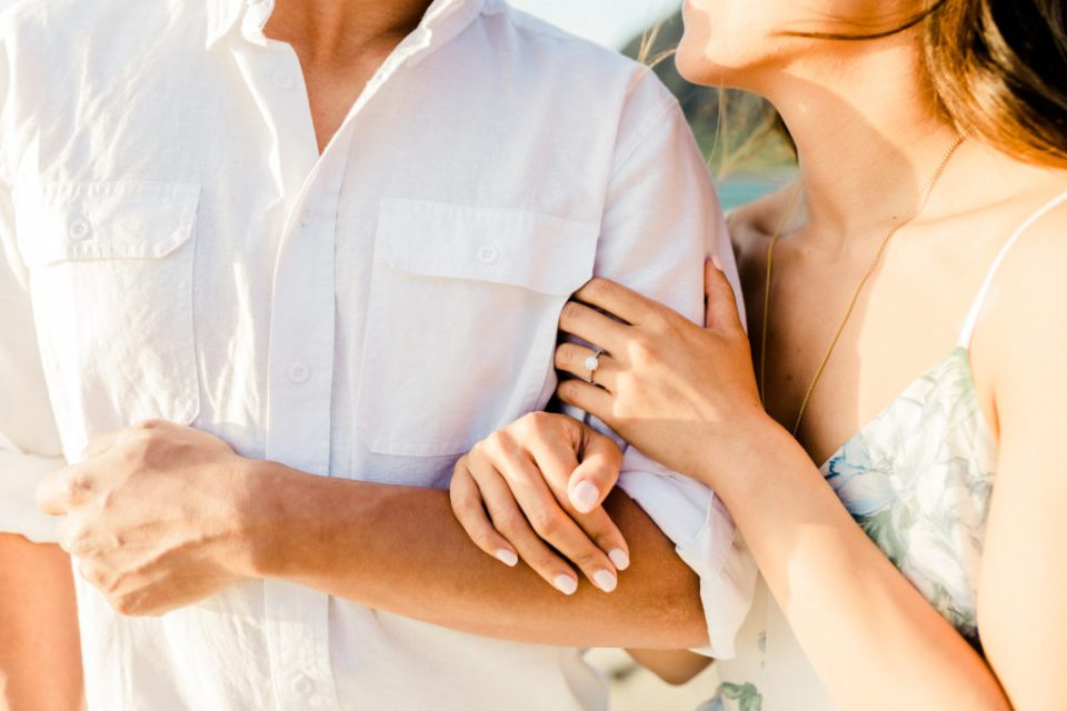 engagement ring at beach session with couple