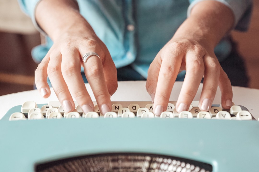 Woman typing on vintage typewriter