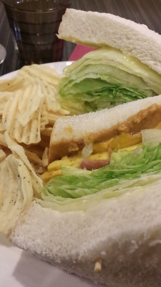 Egg Sandwich with a sauce, lettuce, and peanut butter. Chips on the side.