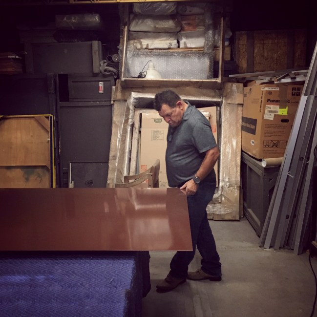 Erre inspecting a newly dry brown panel for his next project.