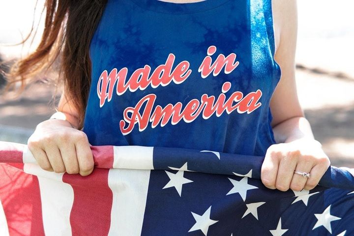 Person with a Made in America shirt holding an American Flag