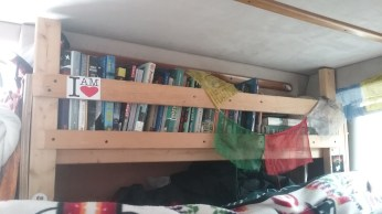 The shelving unit contains two shelves and hidden storage space beneath the lower shelf