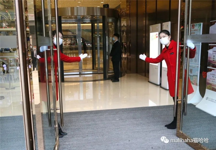 Staff members open doors at Wuhan International Plaza and welcome customers in Wuhan, Central China's Hubei province, on March 30, 2020. [Photo by Zhou Guoqiang/for chinadaily.com.cn]