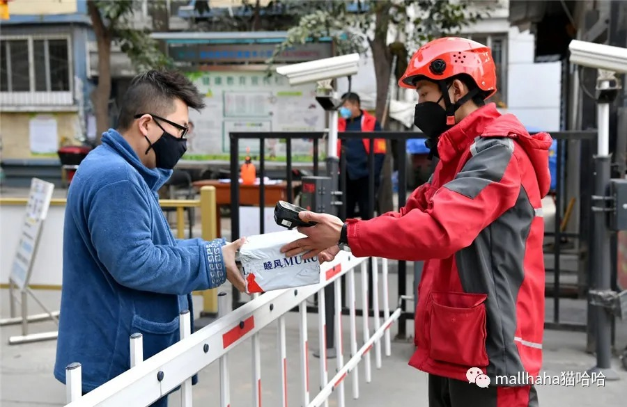 A delivery man, right, hands a package to a resident at the gate of a residential community in Xi'an, capital of Shaanxi province. [Photo/Xinhua]