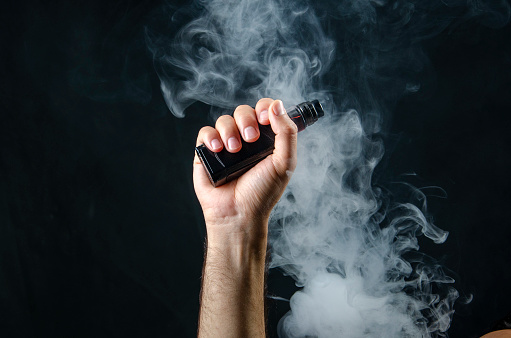 young man hand holding vape e-cigarette or electronic cigarette with white smoke over a black background.