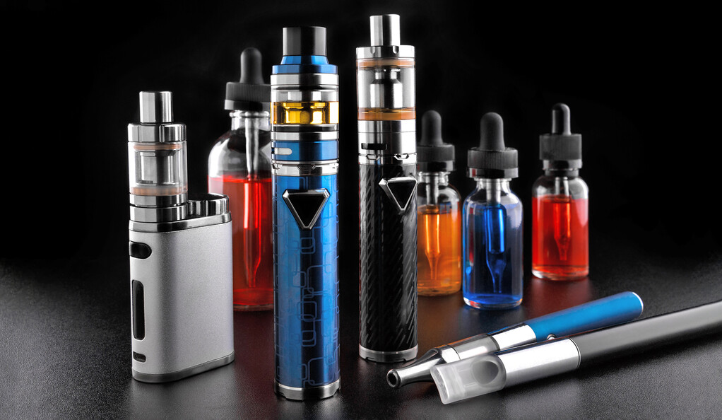Modern electronic cigarettes and bottles with assorted vape liquid on black background