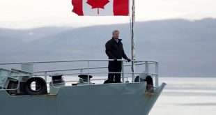 Canadian Prime Minister Stephen Harper stands on the bow of the HMCS Kingston as it sails in the Navy Board Inlet Sunday August 24, 2014. THE CANADIAN PRESS/Adrian Wyld  //  na122314-second