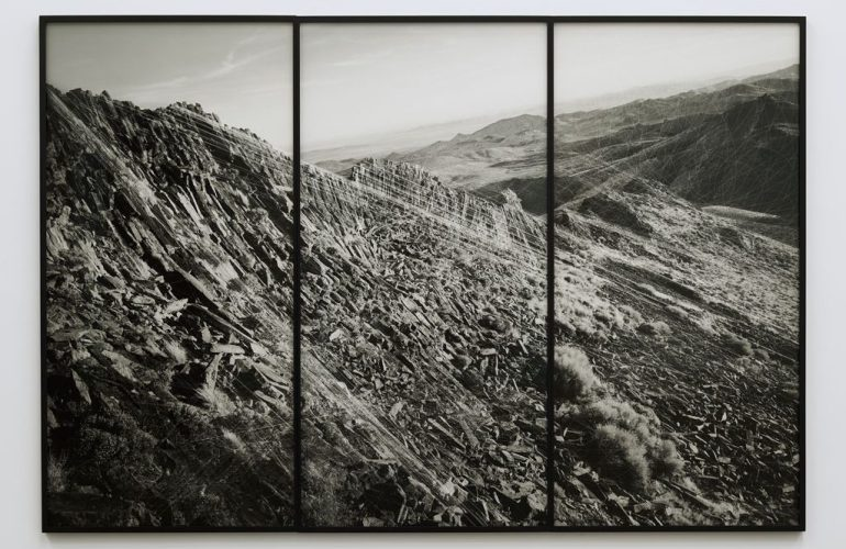 A black and white image of an arid, rocky mountain range split between three tall, vertical, black frames. There are white lines and marks layered over the image, seeming to describe the topography.