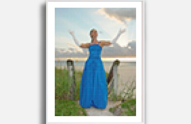 A photograph depicted with intentionally low resolution: the image shows a woman wearing a strapless blue gown and long white gloves. She is standing with her arms raised in front of a staircase that descends to a beach, with the dusky sky over the ocean behind her.