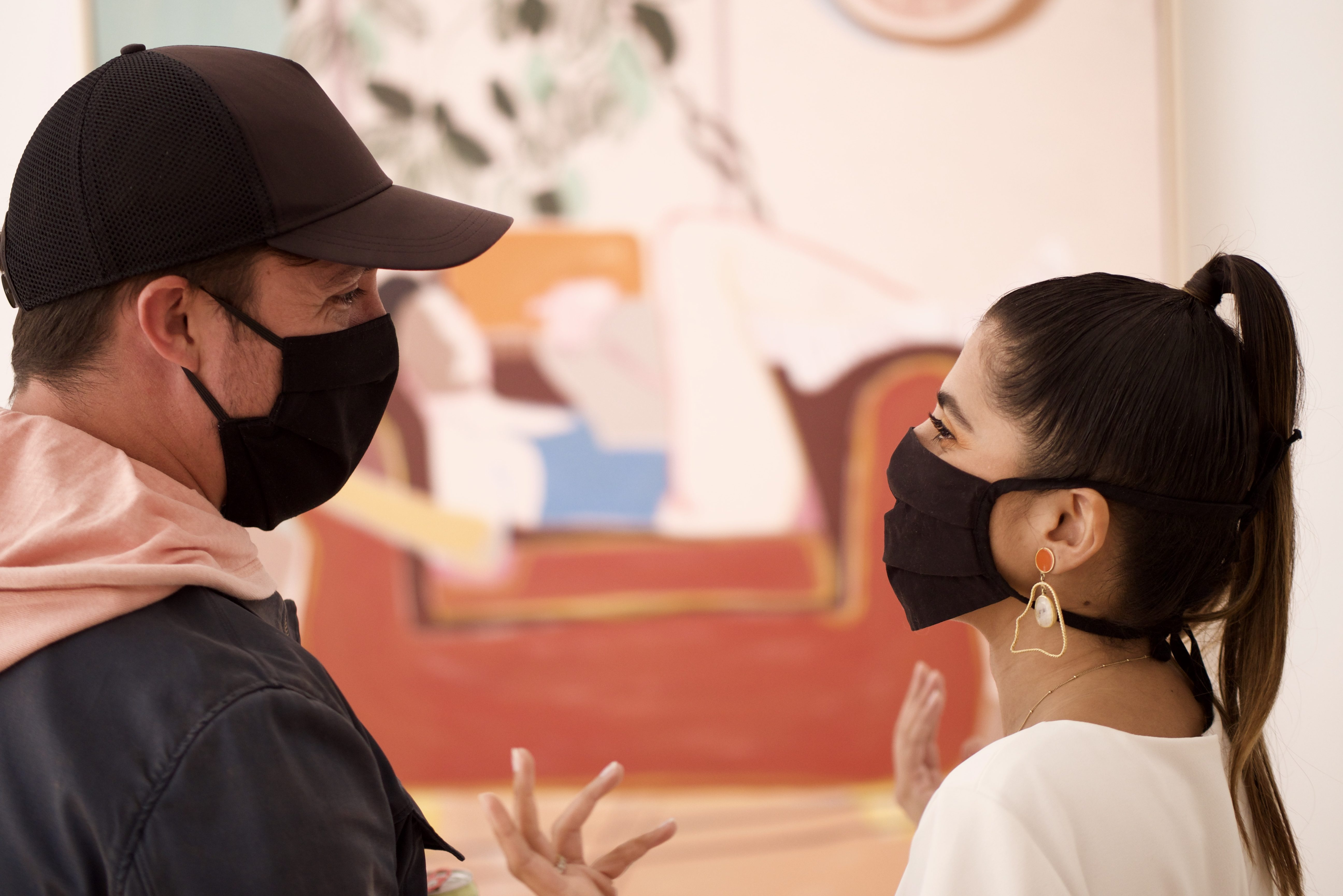 A young woman and a young man talk in front of a painting, blurred in the background. Both are wearing black face masks. The woman has thin, dark hair styled in a high ponytail and is gesticulating with her hands, and her eyes suggest that she is smiling. The man wears a black cap and his eyes suggest that that he is smiling too.