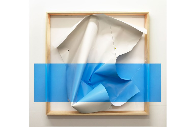 An optical illusion sculpture that consists of a crumpled piece of paper set in a light wood frame with a large, horizontal, blue rectangle seemingly laid over the bottom part of the frame, crumpled paper, and surrounding wall.