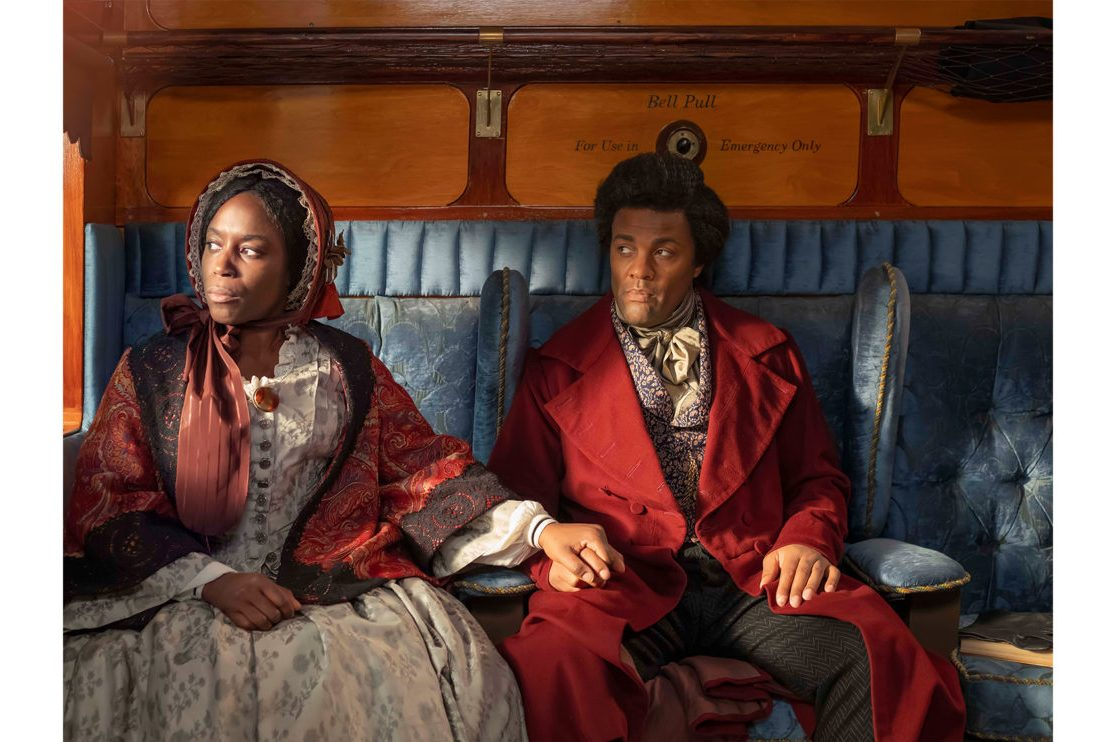 A film still from Isaac Julien's Lesson of the Hour. A Black woman and a Black man dressed in fine nineteenth century fashions sit in a high quality carriage. The woman reaches over to clasp the hand of the man, they both look out the carriage window.