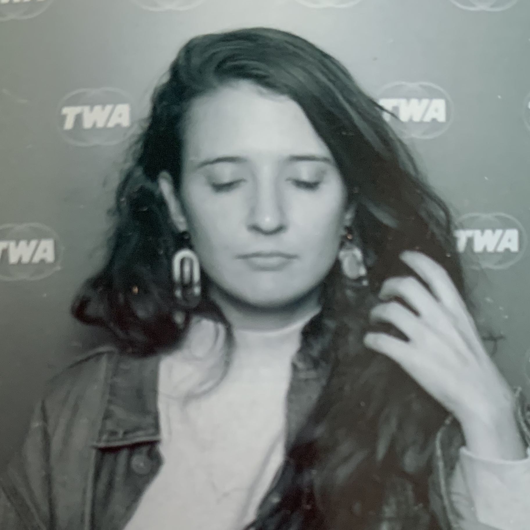 A black and white portrait of Kaitlyn A. Kramer. Her eyes are closed and her left hand brushes back her long dark hair. She's wearing a white mockneck sweater, a denim jacket, and large earrings.