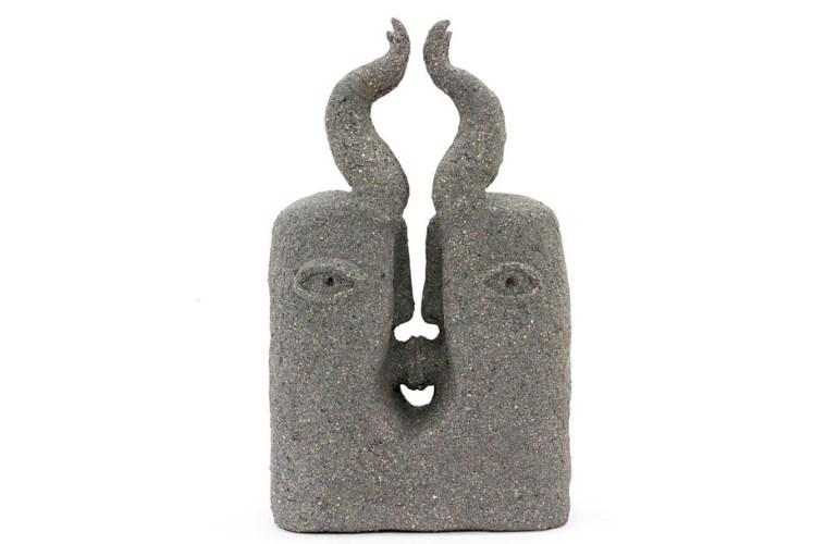A rough, grey, ceramic and porcelain sculpture of a stylized head. The rectangular face has faint, almond-shaped eyes, two horns on the top of the head, with a deep split between the horns extending down to the nose. The head's mouth is a hole that extends through the center of the sculpture.