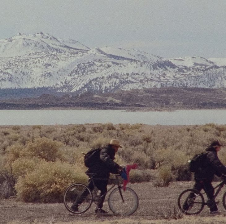 Two people walk bicycles across an arid landscape. There is a snow-covered mountain in the background. A grey river creates a broad stripe through the middle of the frame, reflecting the grey sky.