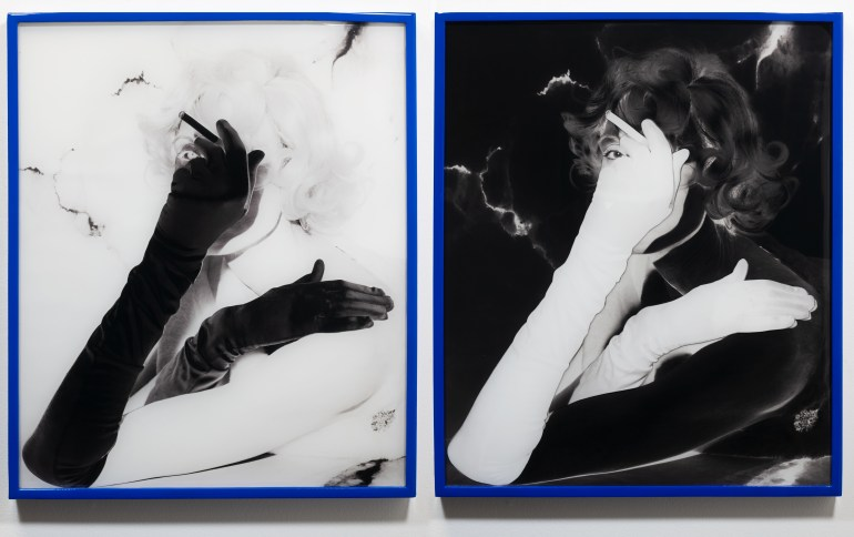 Two photographs displayed site by side in thin, cobalt blue frames. Both are identical black and white portraits of a woman, but the left image is negative and the right image is positive. Shown from the shoulder up, her body is perpendicular to the camera and her face turns toward the camera. Her arms cross in front of her body, with her right hand placed over her left shoulder. Her right hand is raised to cover most of her face, and holds a cigarette.