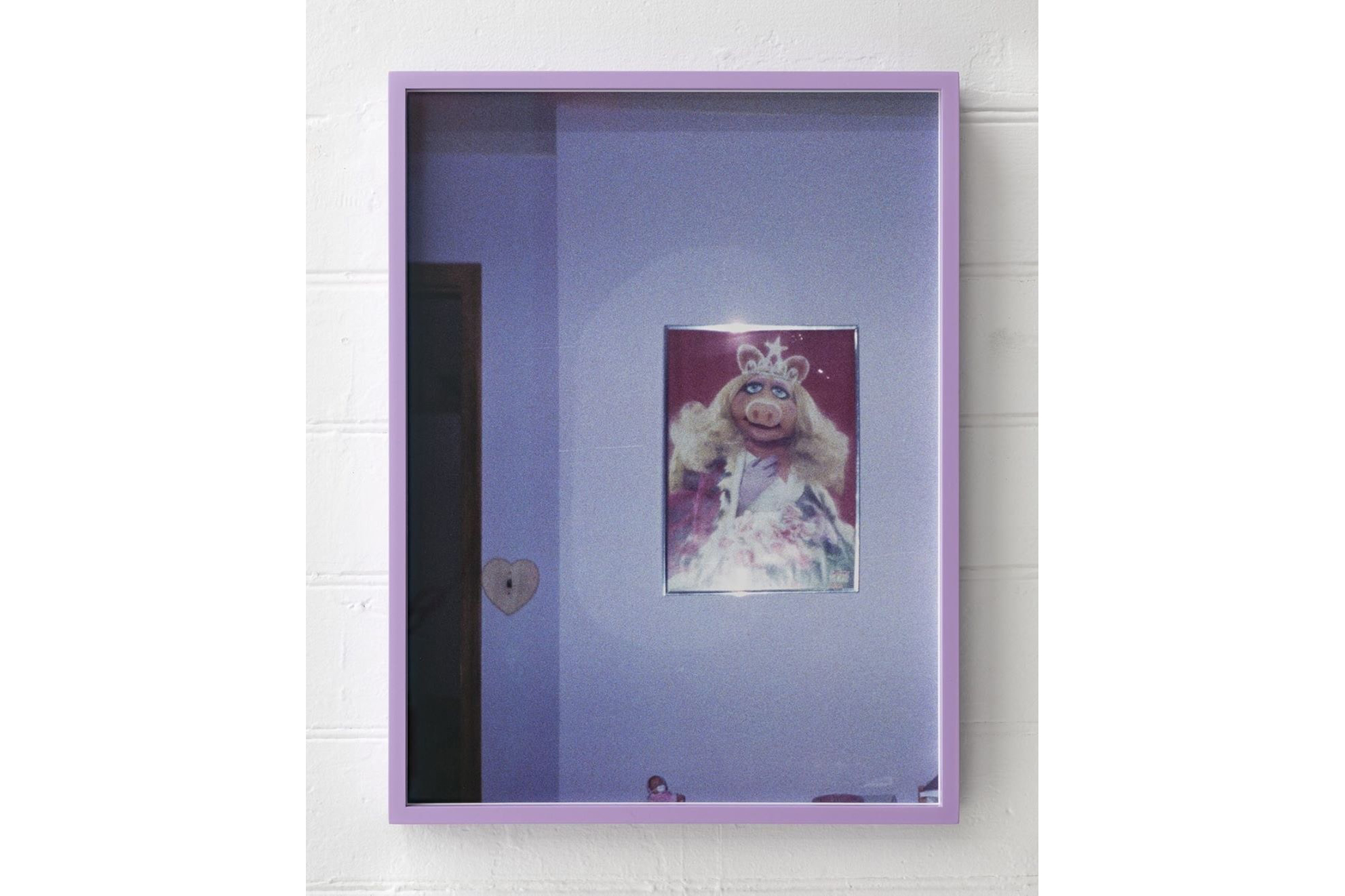 A photograph in a lilac frame hanging on a white wall. The photograph is of a poster of Miss Piggy looking glamorous with a tiara and her blonde hair styled in romantic waves. The poster is in a thin metallic frame with two highlights from the camera's flash. The framed posted hangs on a wall, with a heart-shaped light switch to its left.