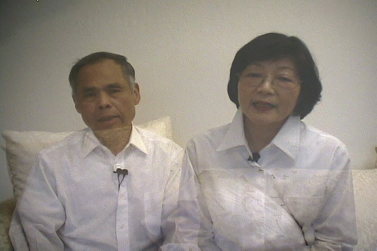 A video still showing a man and a woman in white button down shirts sitting, facing the camera. Their bodies are semi-transparent and overlap at the shoulder. Both have their mouths open as though caught mid-sentence.