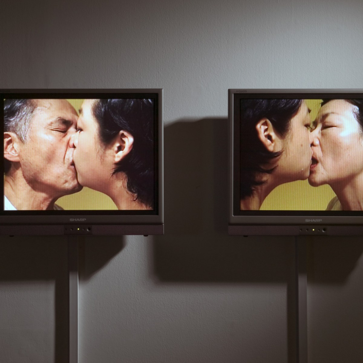 An installation view of two video screens mounted on a wall. The left screen shows a man and a woman kissing in front of a yellow background. The right screen shows two women kissing in front of a yellow background.