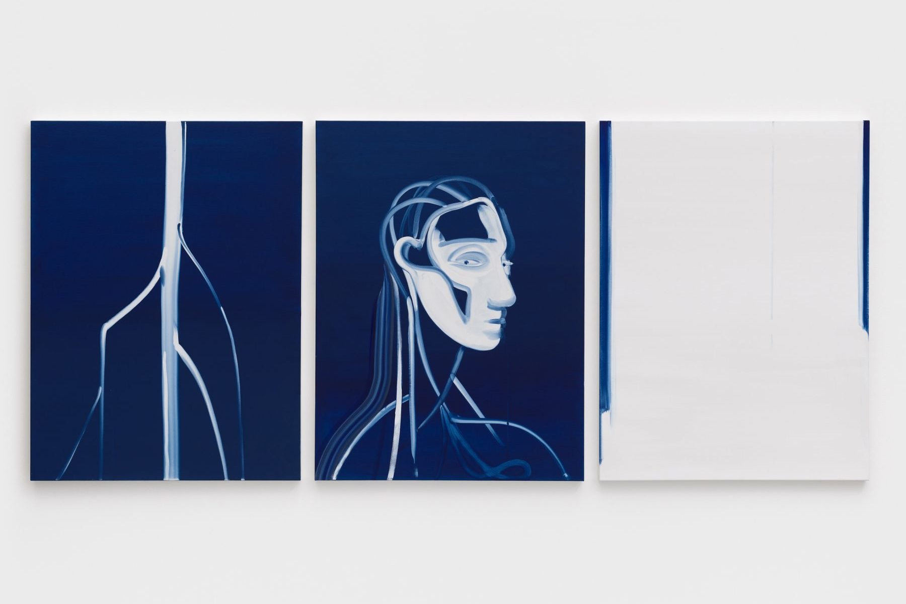 Three paintings hung on a white wall, each in a deep blue and white. The far left painting has a blue background with a white branched object bisecting the canvas. The central painting is a portrait of a android with a white face and transparent head, neck and shoulders with strokes of white. The far right painting is mostly white with two blue strips on each side.
