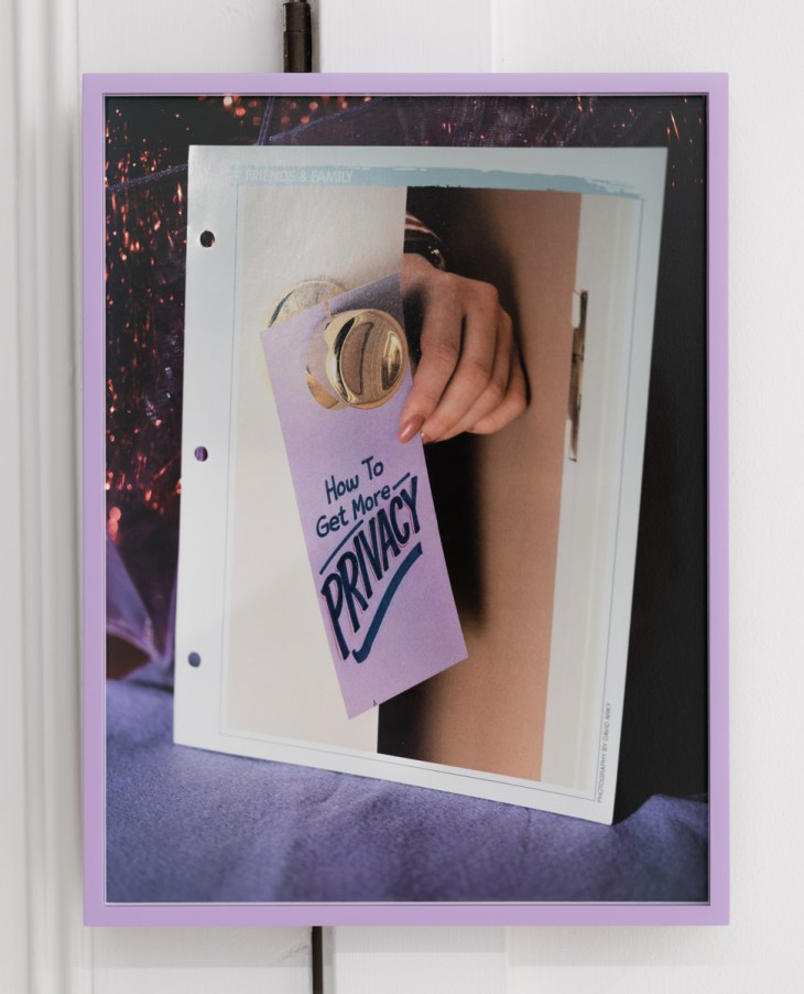 """A re-photographed image, it shows a white woman's beige-manicured hand reaching around a door to place a lavender tag reading """"How to Get More Privacy"""" on the doorknob."""