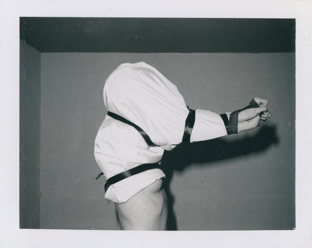 A black and white polaroid photograph of a woman from the waist up, facing to the right with her arms held out in front of her. Her torso is bare up to her breast, which is partially covered by a white shirt or sheet that has been pulled over her head and arms. A dark, satiny, wide ribbon is tightly pulled under her armpits, over her shoulders, around her elbows, and around her wrists.