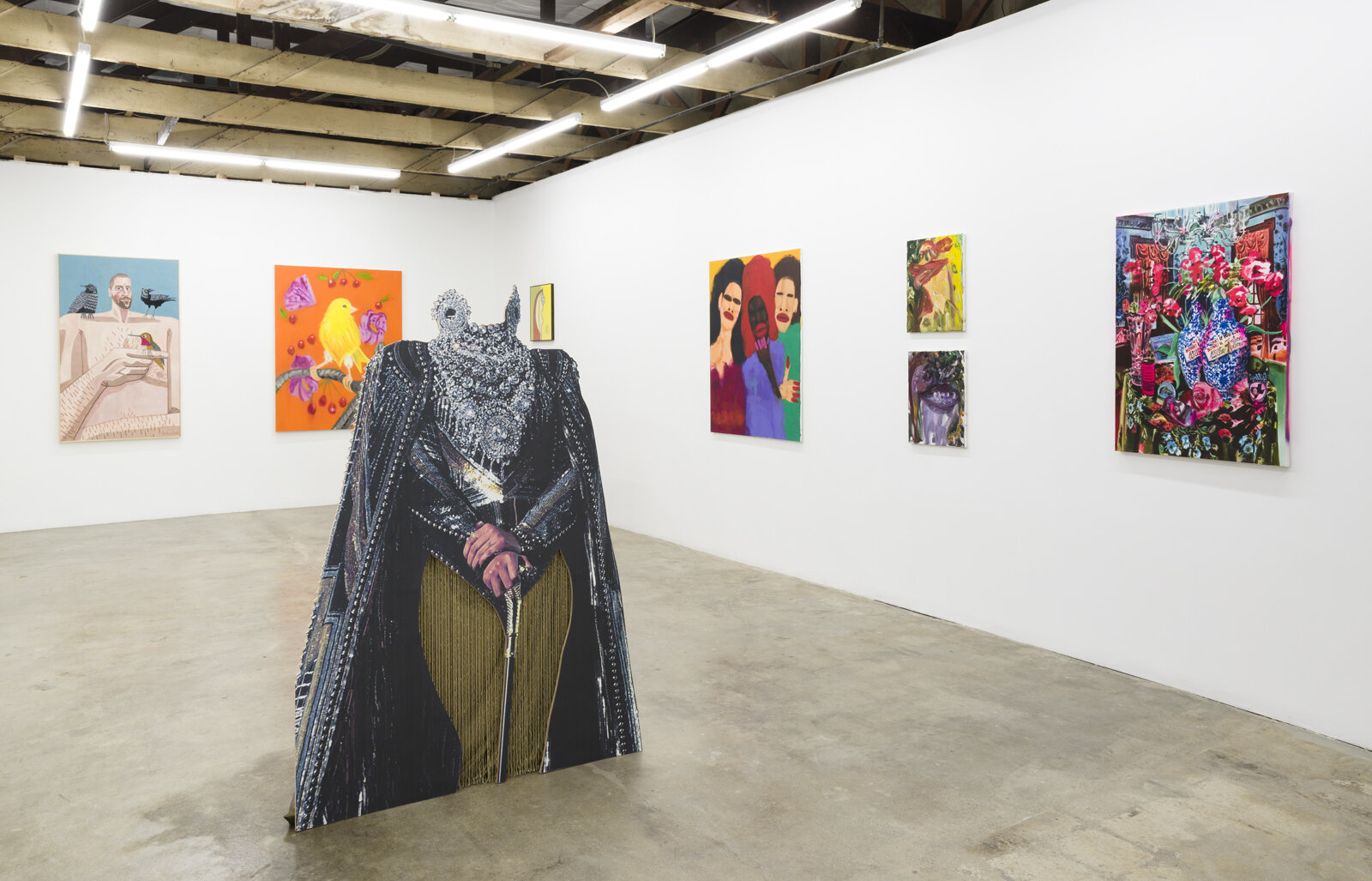 Installation view of Mirror Gazing, featuring paintings hung around white walls and a sculpture in the center of the room. The sculpture is of a woman's body wearing an ornate coat and necklace. The figure's head is missing.