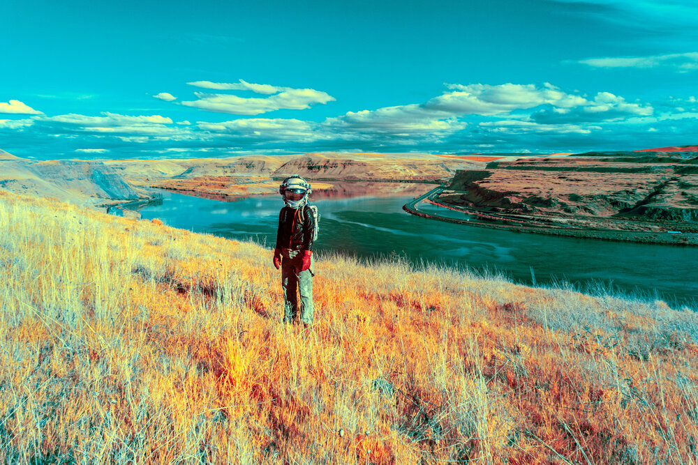 A person in a space helmet stands and civilian clothes in a dry grass field above a canyon with a river running through it. The photograph's colors are surreal, with a turquoise sky and intense saturation.