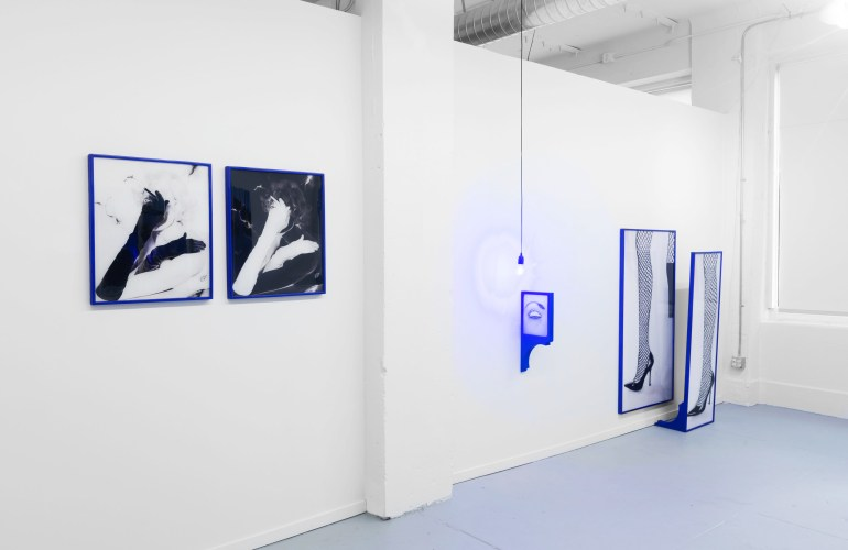 an installation view of Repetition Suppression by Natalie Krick at Specialist gallery in Seattle, WA. Three works occupy a white wall. On the left is a diptych of one image, presented as both negative and positive black and white, in thin, cobalt blue frames. In the center is a black and white image a closed eye in a blue frame that extends perpendicularly out from the wall. A bare lightbulb hangs from the ceiling above it. On the far right there are two large, vertical black and white images of a leg in fishnet stockings and black high heel shoes. One image hangs on the wall in a thin blue frame. The other is in a standing frame, also blue.