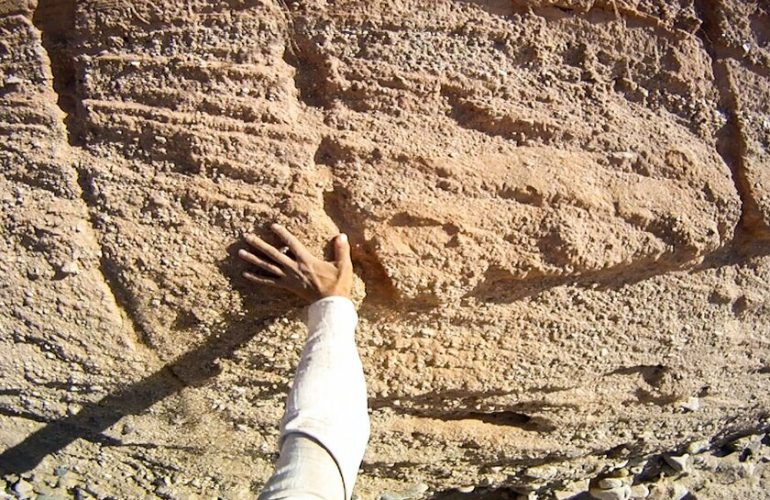 An arm reaches out from the bottom left of the frame to touch a sandy-colored rock wall. The arm has a long sleeve white shirt, the rock wall has grooves and marks of various depths. The image is slightly blurred, indicating that it was taken while the camera-holder was in motion, as if walking.