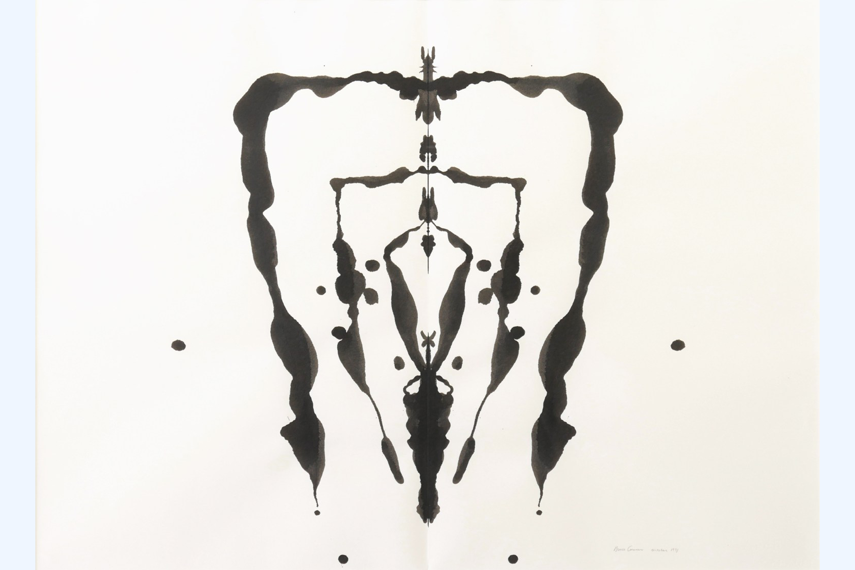Black ink on white paper in an abstract design. The image is symmetrical, each side a mirror image of the other, and appears to be made by placing ink on paper and then folding the paper to create the design.