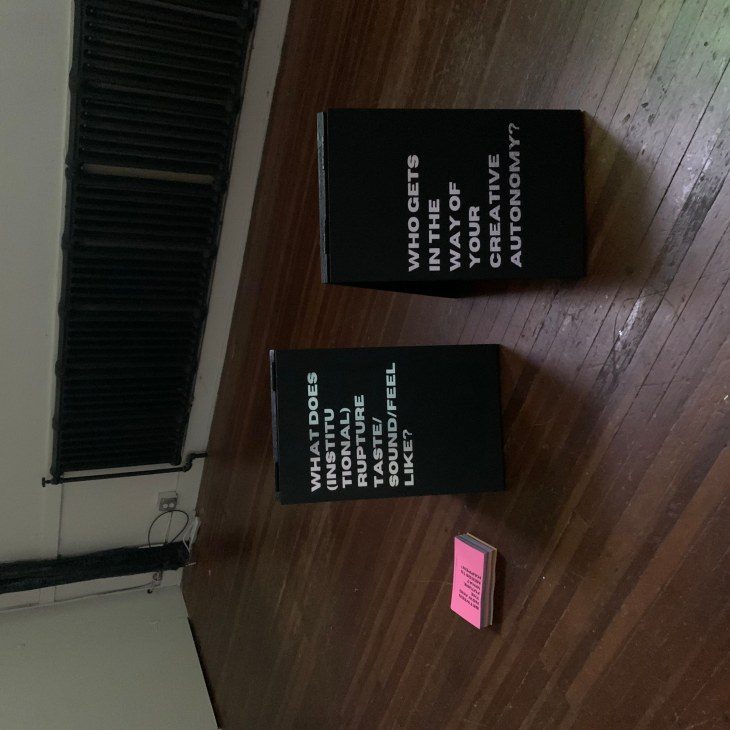 """Two black sandwich board signs on a wood floor. One reads """"What does (Institutional) rupture feel/taste like?"""" The other reads """"Who gets in the way of your creative autonomy?"""" There is a small stack of multi-colored booklets on the floor next to the board on the left."""