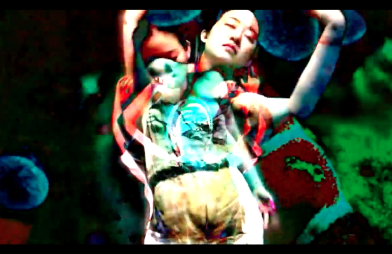 A video still with layered images of a woman dancing. The image has high contrast and pixelated swaths of color in the background.