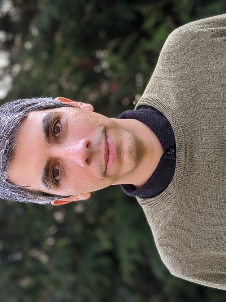 Jaime Salazar standing in front of dark green foliage, blurred in the background. He wears an olive green sweat and black polo shirt. He has salt and pepper grey hair and kind eyes.