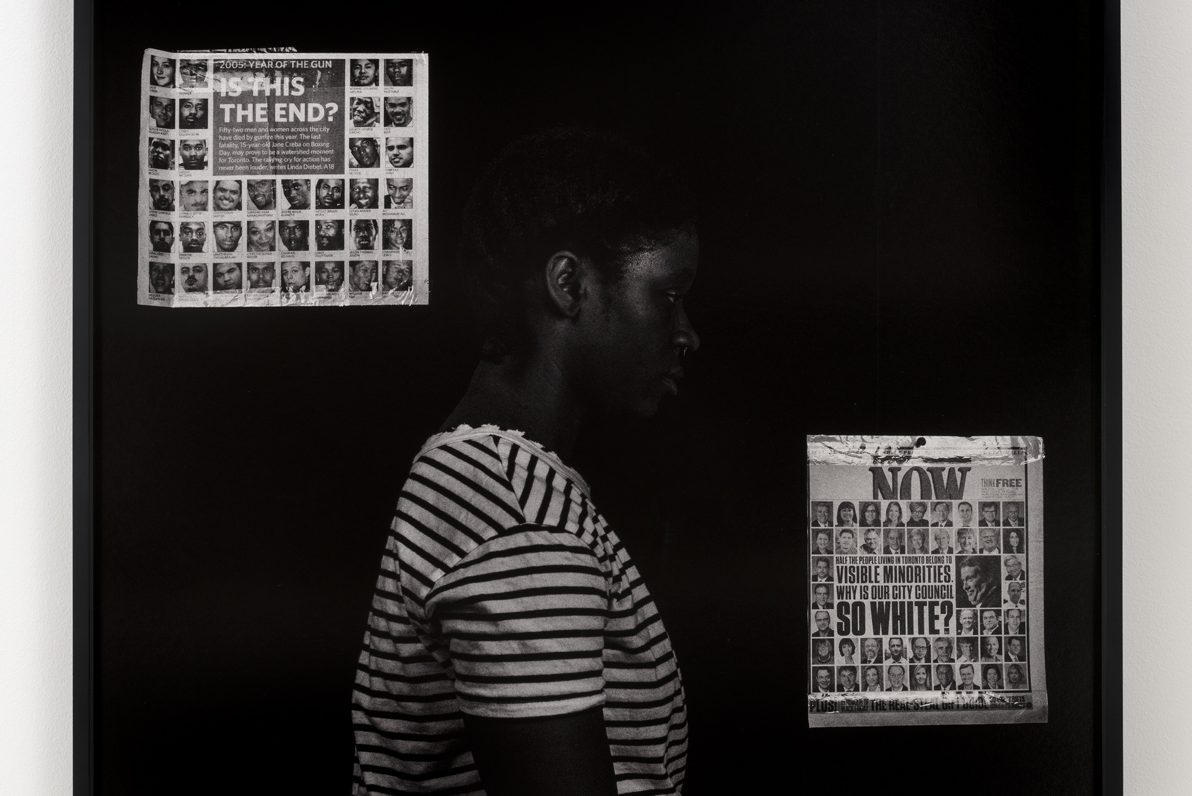 "Photograph hanging on a white wall. Center frame, a Black woman wearing a striped t-shirt stands before a black background, facing to the right, evoking the image of a mugshot. Behind her head on the left hangs a newspaper clipping depicting a grid of headshots of people of color below the words ""IS THIS THE END?"" Just before her torso hangs another clipping, this one a grid with mostly white headshots, reading ""WHY IS OUR CITY COUNCIL SO WHITE?"""