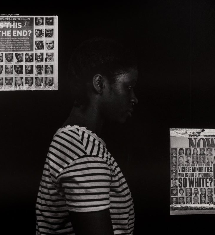 """Photograph hanging on a white wall. Center frame, a Black woman wearing a striped t-shirt stands before a black background, facing to the right, evoking the image of a mugshot. Behind her head on the left hangs a newspaper clipping depicting a grid of headshots of people of color below the words """"IS THIS THE END?"""" Just before her torso hangs another clipping, this one a grid with mostly white headshots, reading """"WHY IS OUR CITY COUNCIL SO WHITE?"""""""