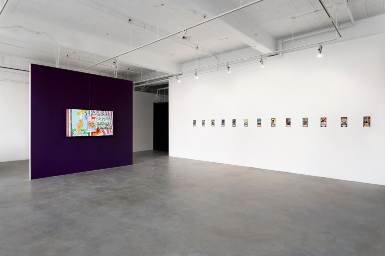 An installation view of Long Con by Ilana Harris-Babou at Jacob Lawrence Gallery in Seattle, WA. A dark purple wall has one large video screen mounted on it. To the right , there is a long line of small rectangular cards hung on the wall.