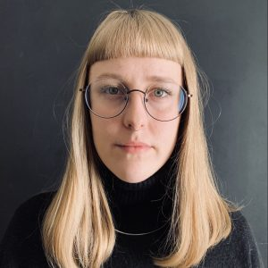 Angela Groom is a woman in her mid-twenties with white skin, green-blue eyes, and short blonde hair with bangs. She is wearing glasses, a silver chain, and a black turtle neck sweater.