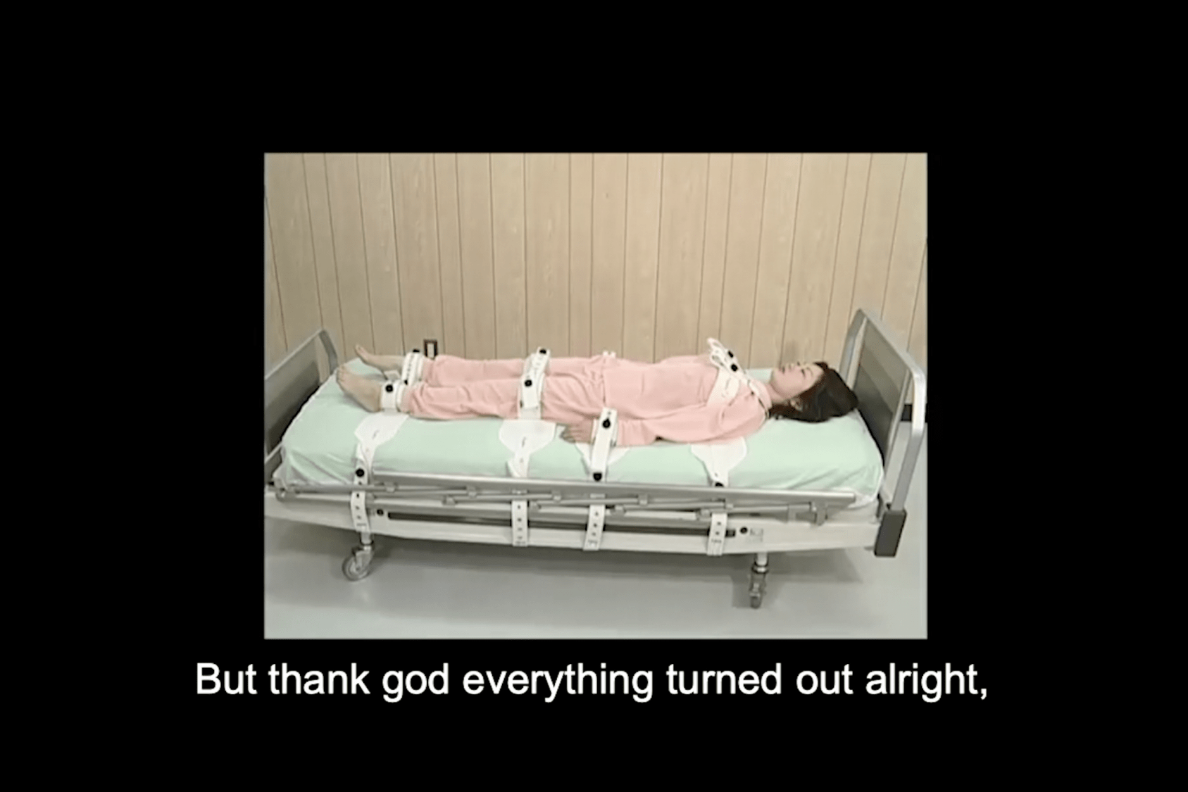 """Woman strapped down to a hospital bed by her ankles, thighs, hands, and chest, her eyes closed. The text below the photo reads """"But thank god everything turned out alright,"""""""