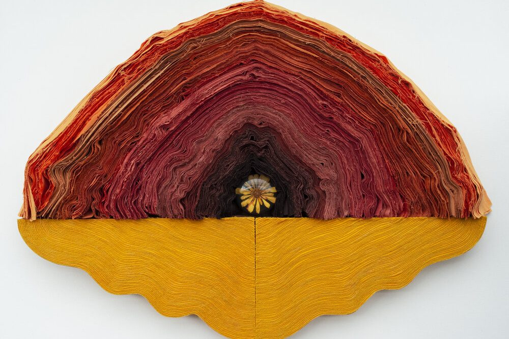A sculpture piecing together layers of fabric and yarn in an oval shape, growing darker nearer the center where lies a resin cast flower, evoking the sensation of an ovular, tectonic inside.