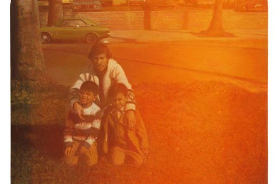 Photorealistic painting of a man crouched on a lawn his arms draped over two children's shoulders. Behind them, a tree, a small car, a parking lot.