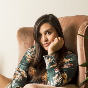 Portrait of Keisha Raines, a brunette with brown eyes in her early thirties, smirking at the camera. She's wearing a long velvet green dress and is sitting in a pink velvet chair.