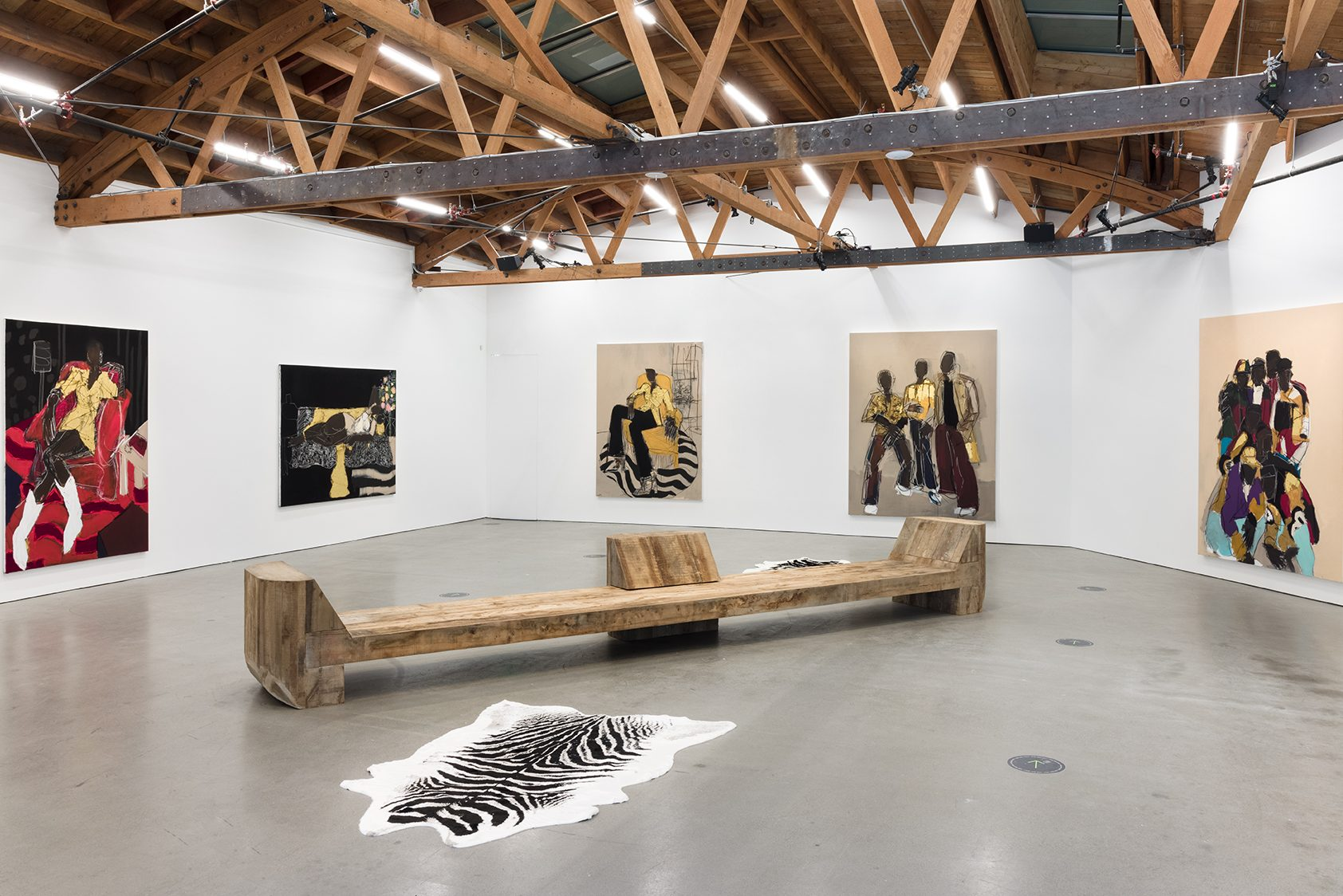 Gallery space with polished concrete floor, geometric white walls under a curved wood ceiling, upheld by exposed wood support beams. Five paintings populate three walls, each striking, full-body portraits of Black individuals, some standing together in groups, some lounging on living room furniture. A long wooden bench stretches out in the middle of the space, next two zebra-print carpets.